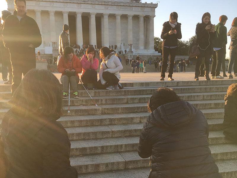 pengambilan gambar Andrea duduk di Lincoln Memorial Amerika bersama temannya